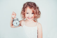 Little girl with the alarm clock Royalty Free Stock Photography