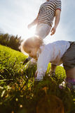 Little girl on all fours in the park Stock Photos