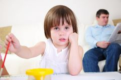 Little girl alone draws Stock Photography