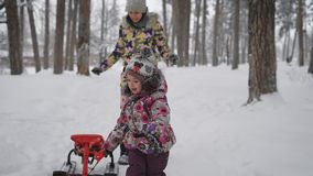 Little girl alone pulling his sleigh through the snow in the park. Young mother on the background watching and helping stock video