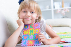 Little girl with alphabet puzzle Stock Photos