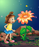 A little girl amazed by the giant flower near the rocks Stock Photo