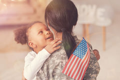 Little girl with American flag whispering to her mothers ear. I love you. Cute little girl with an American flag in her hand hugging her mother in a military stock image