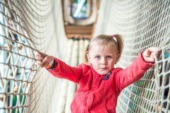 Little girl in amusement park rope tunnel Royalty Free Stock Photo
