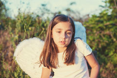 Little girl with angel wings and white dress Stock Photos