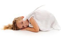 Little girl with angel wings and white dress. Little girl with angel wings resting on the floor in a curled up position - isolated Royalty Free Stock Images