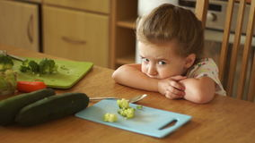 The little girl angrily looks at the broccoli. Not hungry. Protest, lack of appetite. stock video footage