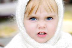 The little girl with an angry face. In a scarf Stock Photo