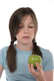 Little Girl and Apple 1. Little girl with pig tails in her hair looking at a green apple royalty free stock photos