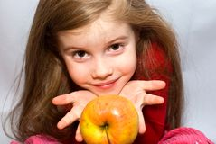 Little girl with an apple. Little girl holding apple in her hands and looks at camera Stock Image