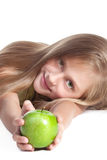 Little girl with an apple. Little blond girl with green eyes holding a green apple Royalty Free Stock Images