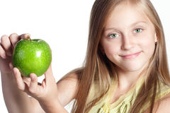 Little girl with an apple. Little blond girl with green eyes holding a green apple Royalty Free Stock Image