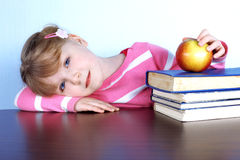 Little girl with apple and books Stock Images