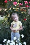 Little girl with Apple among the flowers Royalty Free Stock Photography