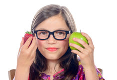 A little girl with an apple and a strawberry Stock Image