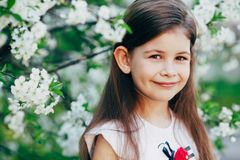 Little girl at apple tree flowers Stock Photo