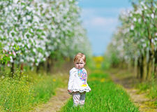 Little girl in an apple-tree garden costs on footpath. royalty free stock photography