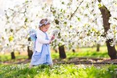 Little girl in apple tree garden stock photo