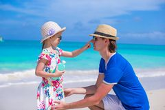 Little girl apply sunscreen on nose of her dad Stock Photo
