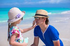 Little girl apply sunscreen on nose of her dad Stock Photography