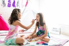 Girl Applying Blush On Friend`s Cheek During Sleepover Party. Little girl applying blush on happy friend`s cheek during sleepover party stock photography