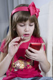 Little girl applying makeup copying mother Royalty Free Stock Images
