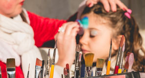 Little girl is applying makeup in a stand Stock Photography