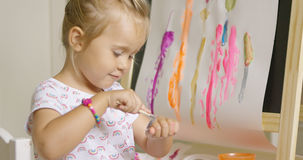 Little girl applying paint to the back of her hand Royalty Free Stock Image