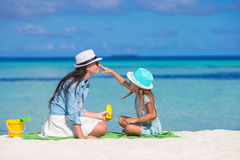 Little girl applying sun cream to her mother nose Royalty Free Stock Photography