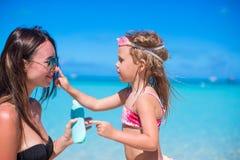 Little girl applying sunblock cream on her mom Stock Image