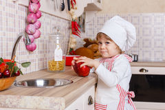 Little girl in apron in the kitchen. Royalty Free Stock Image