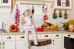 Little girl in apron in the kitchen. Stock Photos