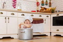 Little girl in apron in the kitchen. Royalty Free Stock Photo