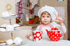 Little girl in apron in the kitchen. Royalty Free Stock Images