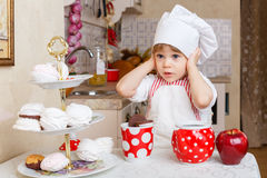 Little girl in apron in the kitchen. Royalty Free Stock Photos