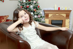 The little girl in the armchair by the Christmas tree. Adorable little girl new year`s eve on the backdrop of the Christmas tree sits on a leather armchair Royalty Free Stock Images