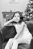 The little girl in the armchair by the Christmas tree. Royalty Free Stock Image