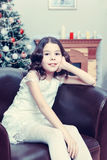 The little girl in the armchair by the Christmas tree. Adorable little girl new year`s eve on the backdrop of the Christmas tree sits on a leather armchair Royalty Free Stock Photos