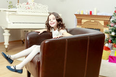 The little girl in the armchair by the Christmas tree. Royalty Free Stock Photos