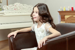 The little girl in the armchair by the Christmas tree. Stock Images