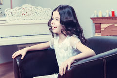 The little girl in the armchair by the Christmas tree. Stock Image