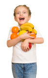 Little girl with armful fruits Stock Photo