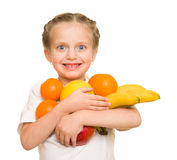 Little girl with armful fruits Royalty Free Stock Photo