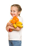 Little girl with armful fruits Royalty Free Stock Image