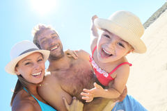 Little girl in the arms of the parents on the beach Stock Photography