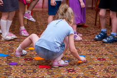 Little girl arranges colored shapes on carpet Royalty Free Stock Photos