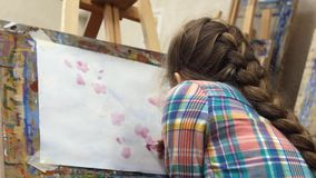 Little girl artist draws at the easel. Drawing process: close-up of brush and canvas. Close up stock footage