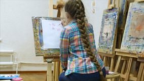 Little Girl artist draws at the easel. Drawing process: close-up of brush and canvas. stock video