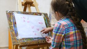 Little girl artist draws at the easel. Drawing process: close-up of brush and canvas. Close up stock video footage