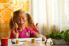 Little girl artist with paint of face. Stock Photo